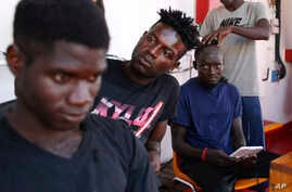 A migrants get his head shaved aboard the Ocean Viking humanitarian rescue ship, in the Mediterranean Sea, Sept. 12, 2019.