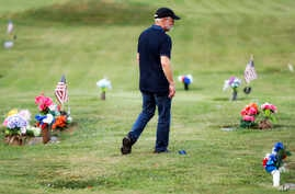 Eddie Davis walks past tributes on his way to his son Jeremy's gravestone, who died from the abuse of opioids, July 17, 2019, in Coalton, Ohio.