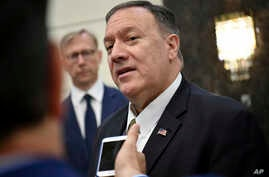 U.S. Secretary of State Mike Pompeo speaks to the media before departing from al-Bateen Air Base in Abu Dhabi, United Arab Emirates, Sept. 19, 2019, as U.S. special representative on Iran Brian Hook, left, listens.