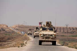U.S. armored vehicles travel in a joint patrol of the safe zone between Syria and the Turkish border with the Tal Abyad Military Council near Tal Abyad, Syria, Sept. 6, 2019.