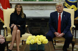 First lady Melania Trump listens as President Donald Trump talks about a plan to ban most flavored e-cigarettes, in the Oval Office of the White House, Sept. 11, 2019, in Washington.