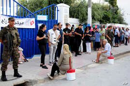 Security forces stand guard as voters queue outside a polling station during the first round of the presidential election, in La Marsa, outside Tunis, Tunisia, Sept. 15, 2019.