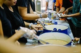 Staff and volunteers hand out meals at the Pit Stop Community Café in Kuala Lumpur, Malaysia. (Courtesy - Pit Stop Community Café)