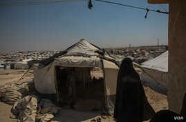 A woman walks among the thousands of tents at Al-Hol Camp. Here, the Islamic rules implemented by IS are still followed as they were under the group, Aug. 26, 2019. (Yan Boechat/VOA)