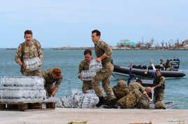 Members of the Humanitarian and Disaster Relief (HADR) team from the Royal Fleet Auxiliary's RFA Mounts Bay deliver supplies after Hurricane Dorian on the island of Great Abaco, Bahamas, Sept. 4, 2019.