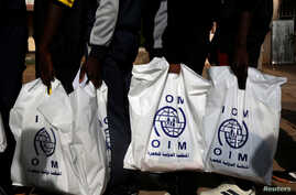 FILE - Gambian migrants repatriated from Libya stand in line with plastic bag from the International Organization for Migration (IOM) as they wait to be registered at the airport in Banjul, Gambia, April 4, 2017.