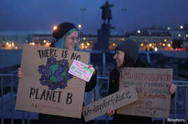 FILE - Activists with signs are an environmental rally, part of the Global Climate Strike, in Saint Petersburg, Russia, Sept. 20, 2019.