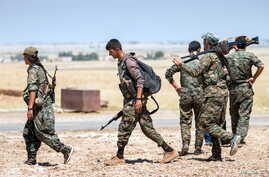 Kurdish fighters walk with their weapons outside the town of Tal Abyad, Syria, June 14, 2015.