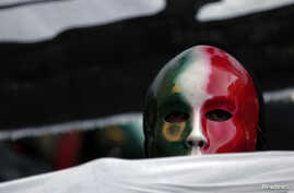 """FILE - A member of the Casapound far-right organization wears a mask in the colors of the Italian flag before a demonstration organized by """"People from pitchfork movement"""" to protest against economic insecurity and the government in Rome, Dec. 18, 2013."""