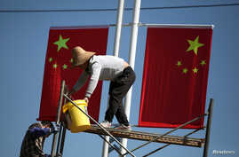 Workers hang up Chinese flags on a street ahead of the 70th founding anniversary of People's Republic of China in Kunming, Yunnan province, China, Sept. 22, 2019.