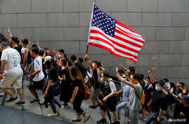 Protesters hold up their hands to symbolize five demands and a U.S. flag during a rally to the U.S. Consulate General in Hong Kong, Sept. 8, 2019.