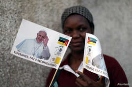 A women poses with flags bearing the face of Pope Francis outside a Catholic church in Lhanguene, Maputo, Mozambique, Aug. 31, 2019.