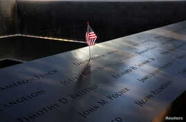 An American flag is seen left in the engraved names of 9/11 victims at the edge of the north reflecting pool at the 9/11 Memorial in lower Manhattan, New York, Sept. 11, 2019.