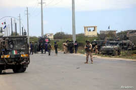 Italian and Somali security forces are seen near armored vehicles at the scene of an attack on a Italian military convoy in Mogadishu, Somalia, Sept. 30, 2019.