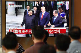 People watch a television news screen showing live footage of US President Donald Trump, South Korean Moon Jae-in and North…