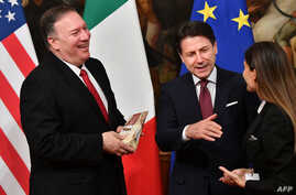 U.S. Secretary of State Mike Pompeo, left, holds a package of Parmesan cheese as Italy's Prime Minister Giuseppe Conte reacts, after the package was handed to Pompeo by Italian journalist Alice Martinelli, right, in Rome, Oct. 1, 2019.