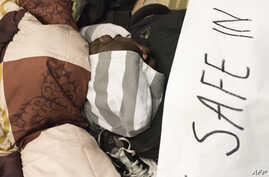 """A man sleeps close to a banner reading """"We are not safe in South Africa, plz help us to leave this country"""" where dozens of…"""