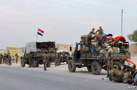 Military vehicles transporting Syrian regime troops and rolled up mattresses are stationed on the outskirts of the northern…