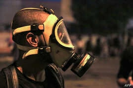A protester wears a gas mask during anti-government protests in the Shiite shrine city of Karbala, south of Iraq's capital…