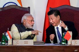 Indian Prime Minister Narendra Modi, left, talks with Chinese President Xi Jinping at the signing ceremony by foreign ministers during the BRICS summit in Goa, India, Oct. 16, 2016.
