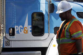 FILE - In this Aug. 15, 2019, file photo, a Pacific Gas & Electric worker walks in front of a truck in San Francisco. Pacific…