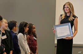FILE - Melania Trump talks with third- and fourth-graders from the United Nations International School during a tour of the New York Stock Exchange in New York, Sept. 23, 2019.