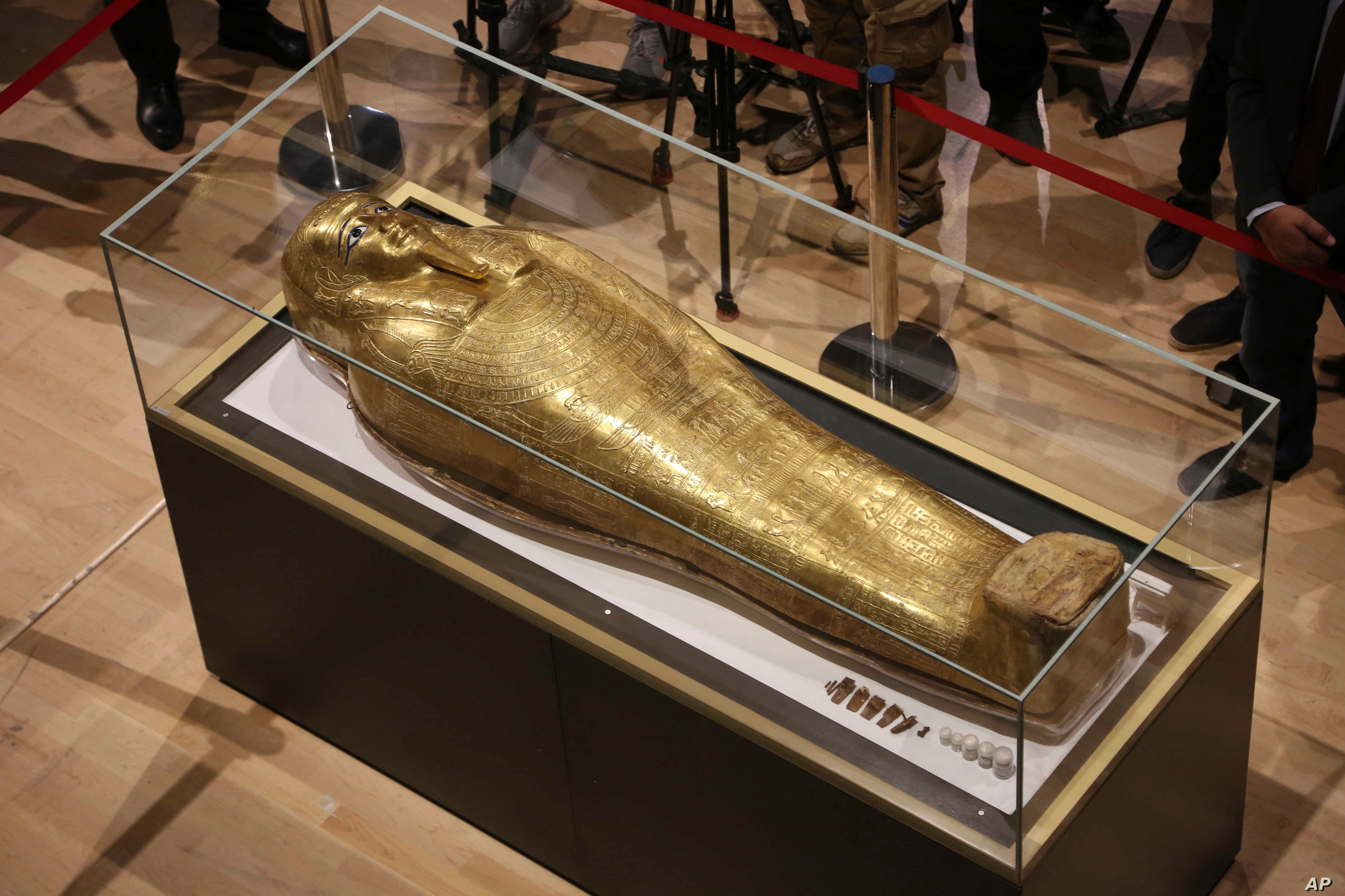 Journalists gather around the golden coffin that once held the mummy of Nedjemankh, a priest in the Ptolemaic Period some 2,000 years ago, at the National Museum of Egyptian Civilization, in Old Cairo, Egypt, Oct. 1, 2019.
