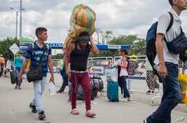 """A man carries a large load on his back, with the strap around his forehead, as he works as a """"lomo taxista,"""" or taxi of the lower back, across the border from Cucuta, Colombia to Venezuela, Sept. 20, 2019."""