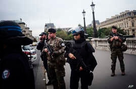 Armed police officers and soldiers patrol after an incident at the police headquarters after in Paris, Oct. 3, 2019.