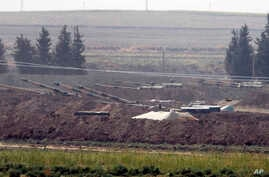 In this Oct. 6, 2019 photo, Turkish forces artillery pieces are seen on their new positions near the border with Syria in Sanliurfa province, Turkey.
