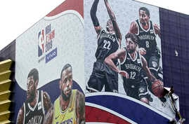 A worker takes down a billboard advertising an NBA preseason basketball game on Thursday between the Los Angeles Lakers and Brooklyn Nets in Shanghai, China, Oct. 9, 2019.