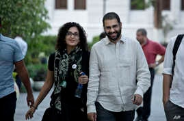 FILE - Alaa Abdel-Fattah, a leading pro-democracy activist, walks with his sister Mona Seif prior to a conference at the American University in Cairo, near Tahrir Square, Egypt, Sept. 22, 2014.