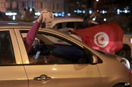 Peopel celebrate with a poster of Kais Saied and Tunisian flags in Tunis, Oct. 13, 2019. Tunisian polling agencies are forecasting that conservative law professor Kais Saied has overwhelmingly won the North African country's presidential election.