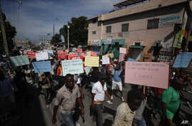Several hundred protesters march carrying signs in Creole calling for President Jovenel Moïse to resign so that schools can…