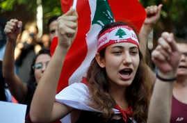 Protester chant slogans during ongoing protests against the Lebanese government, in front of the central bank, in Beirut,…