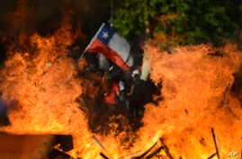 Seen through a burning street barricade, an anti-government demonstrator waves a Chilean flag in Santiago, Chile, Oct. 28, 2019.