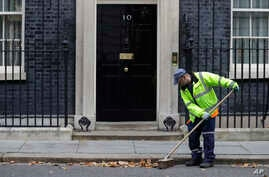 A workman sweeps up leaves in front of 10 Downing Street in London, Oct. 30, 2019.