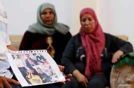 Mokhtar Hmidi, the father of Fakher, who is still unaccounted for after the capsizing of a migrant boat, shows pictures of his son, with Fakher's mother in the background, in Thina district of Sfax, Tunisia Oct. 15, 2019.