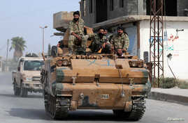 Turkey-backed Syrian rebel fighters ride on a military truck at the border town of Tel Abyad, Syria, October 14, 2019. REUTERS…