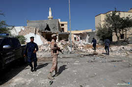 Security members inspect the site of an overnight air strike, which hit a residential district in Tripoli, Libya October 14,…
