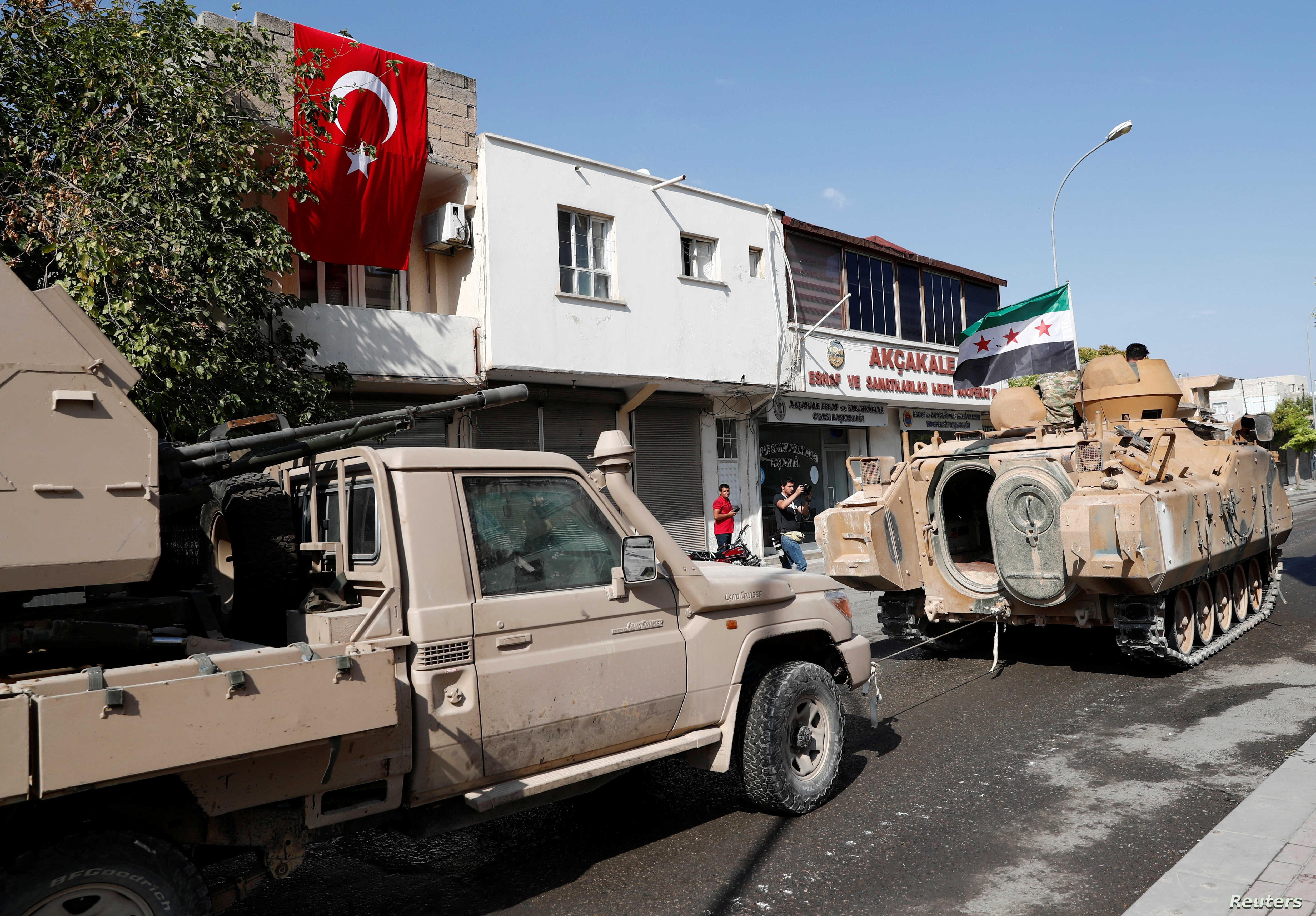 Turkey-backed Syrian rebel fighters return from the Syrian border town of Tal Abyad as they are pictured in Akcakale in…
