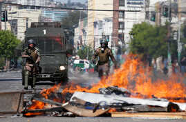 Members of the security forces walk near a burning barricade during a protest, in Valparaiso, Chile October 22, 2019. REUTERS…