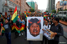 People carry a placard depicting Bolivian President Evo Morales with red horns during a protest march in La Paz, Bolivia…
