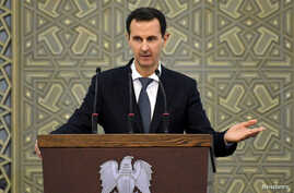 Syria's President Bashar al-Assad speaks during a meeting with heads of local councils, in Damascus, Syria in this handout…