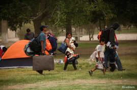 Mexicans camping near the Cordova-Americas international border crossing bridge while waiting to apply for asylum to the U.S., gather their belongings as they are moved to a shelter due a storm forecast, in Ciudad Juarez, Sept. 30, 2019.