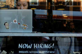 "FILE PHOTO: A ""Now Hiring"" sign sits in the window of Tatte Bakery and Cafe in Cambridge, Massachusetts, U.S., February 11,…"