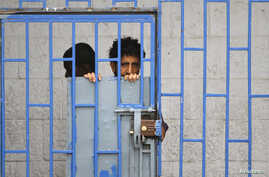 A patient looks from behind bars at a psychiatric hospital during a ceremony marking the World Mental Health Day in Sanaa, Yemen October 10, 2019.