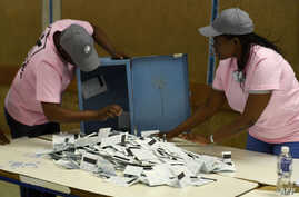 Polling officers verify ballots from ballot boxes arriving at a counting center in the Ledumang Senior Secondary school for the Gaborone North constituency, in Gaborone, Oct. 23, 2019.