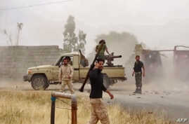 FILE - An image grab from a video reportedly shows fighters of Libyan  military strongman Khalifa Haftar's self-proclaimed Libyan National Army on a road south of the capital Tripoli, May 26, 2019.