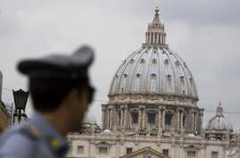 FILE - An Italian financial police officer patrols the road leading to St. Peter's Square at the Vatican, Sept. 21, 2010.